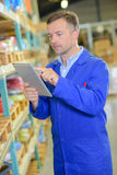 Worker in warehouse using tablet Royalty Free Stock Images
