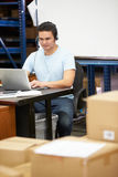 Worker In Warehouse Wearing Headset And Using Laptop. Male Worker In Warehouse Wearing Headset And Using Laptop Royalty Free Stock Photo