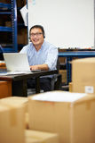 Worker In Warehouse Wearing Headset And Using Laptop. Male Worker In Distribution Warehouse Using Laptop Smiling To Camera Royalty Free Stock Photos