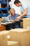 Worker In Warehouse Wearing Headset And Using Laptop. Male And Female Workers In Warehouse Wearing Headset And Using Laptop Stock Photos