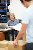 Worker In Warehouse Wearing Headset And Using Laptop. Male And Female Workers In Warehouse Wearing Headset And Using Laptop Royalty Free Stock Image