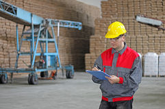 Worker in warehouse. Worker writing on clipboard in warehouse, sugar bags Royalty Free Stock Photography