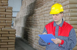 Worker in warehouse. Worker writing on clipboard in warehouse, sugar bags Stock Photography