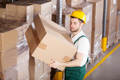 Worker in warehouse. Young male worker is holding box in warehouse Stock Images