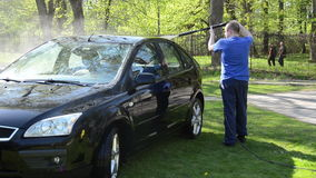 Worker wash black car outdoor with high pressure water equipment stock video footage