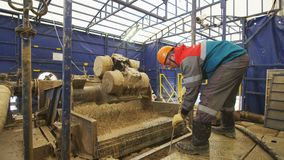 Worker washes samples in dredge machine for geological exploration on site. KAZAN, TATARSTAN RUSSIA - APRIL 17 2018: Worker in rubber boots washes rock samples stock video footage
