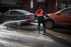 A worker washes the street in places where cars are parked. St. Petersburg, Russia - April 8, 2017: A male utility employee washes the roadside where cars are Stock Photos
