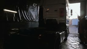 Worke washes truck with water. Worker washes the truck with water. Man holds hose in hands and cleaning the lorry at car service station. Shooting from the stock footage
