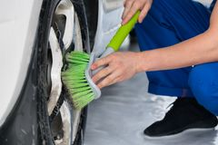 Worker washes the wheel of the car with a green brush soap royalty free stock photography