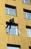 Worker washes windows. Worker cleans the building with the help of water pressure Royalty Free Stock Photography