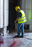 Worker washing industrial site. Worke washing industrial site with an pressure washer Royalty Free Stock Photography