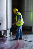Worker washing industrial site. Worke washing industrial site with an pressure washer Stock Images