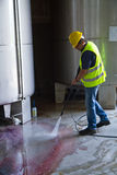 Worker washing industrial site. Worke washing industrial site with an pressure washer Stock Photography