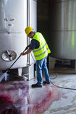 Worker washing industrial site. Worke washing industrial site with an pressure washer Royalty Free Stock Image