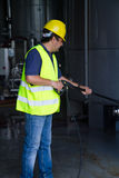 Worker washing industrial site. Worke washing industrial site with an pressure washer Stock Image