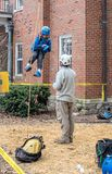 Worker watching child flying in the air in a harness. March 17, 2019  New Carlisle Indiana USA; a worker watches as a child in a harness learns what it is like stock photo