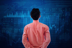 Worker watching at stock exchange graph. Young businessman with formal suit, looking at stock exchange graph Royalty Free Stock Photos