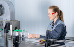 Worker at a water factory. Female worker at a water bottling factory near conveyor royalty free stock photography