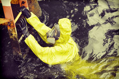 Worker in water reaching ladder to save his life. Worker in protective suit in sea reaching ladder to save his life royalty free stock photo