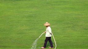 Worker watering the grassland Stock Photo