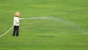 Worker watering the grassland Royalty Free Stock Images