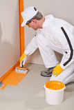 Worker waterproofing. Around the wall and floor before tilling Royalty Free Stock Images