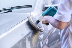 Worker waxing a car with auto polisher Royalty Free Stock Image