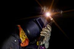 Welding factory. Worker wear protection mask welding steel pipe by tig welding on dark tone Royalty Free Stock Photos