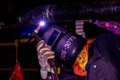 Welding tig argon. Worker wear protection mask welding steel pipe by tig welding on dark tone Royalty Free Stock Photo