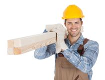 Worker wearing hard hat and carrying timber Stock Image