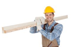Worker wearing hard hat and carrying timber Royalty Free Stock Images