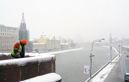 Worker clears the bridge border from snow Royalty Free Stock Photo
