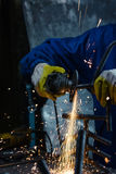 Worker wearing protection equipment using an angle grinder on metal. Horizontal Stock Image