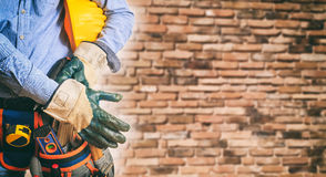 Worker wearing safety equipment. Worker with safety equipment on brick wall background Royalty Free Stock Photography
