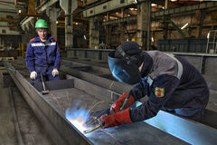 Worker welder manually weld steel sheets using gas torch, MIG. Stock Image