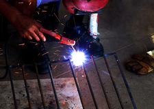 Worker welding connecting square bar Stock Images