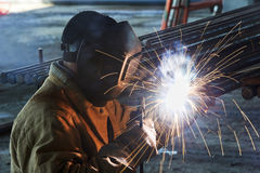 Worker welding with electric arc electrode Stock Photos