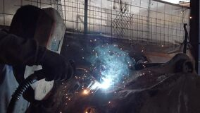 Welder in protective mask works with metal steel