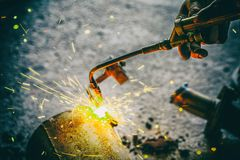 Worker welding joint steel exhaust pipe car. Worker welding joint steel exhaust pipe of the car Royalty Free Stock Photo