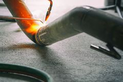 Worker welding joint steel exhaust pipe car. Worker welding joint steel exhaust pipe of the car Stock Images