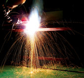 Worker welding metal. Worker in protective clothing welding metal with dark background, colorful sparks and motion blur Royalty Free Stock Photo