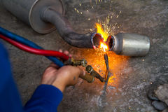 Worker welding metal exhaust pipe with sparks Stock Photos