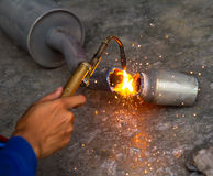 Worker welding metal exhaust pipe with sparks Royalty Free Stock Photos