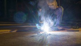 Worker welding metal, focus on flash light line of sharp spark,i Royalty Free Stock Photography