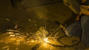 Worker welding metal, focus on flash light line of sharp spark,i Royalty Free Stock Image