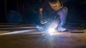 worker welding metal, focus on flash light line of sharp spark,in low light stock photography
