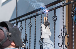 A worker welding metal handrails on the stairs. Ukraine. A worker welding metal handrails on the stairs. Wrought iron railings. Private house. Ukraine stock image