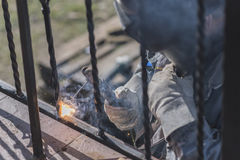 A worker welding metal handrails on the stairs. Ukraine. A worker welding metal handrails on the stairs. Wrought iron railings. Private house. Ukraine stock photos