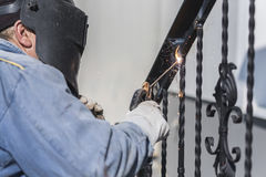 A worker welding metal handrails on the stairs. Ukraine. A worker welding metal handrails on the stairs. Wrought iron railings. Private house. Ukraine stock photography