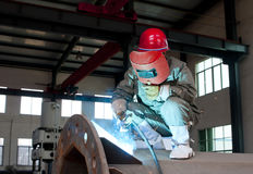 Worker welding a metal lattice at. Worker welding by electrode a metal lattice reinforcement for concrete pouring royalty free stock photography